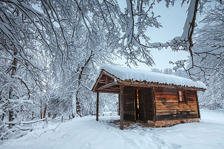 Wooden chapel in snowy forest
